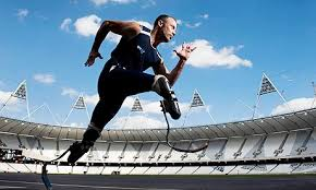 The Wondrous. Action photo of male runner with bilateral high-tech racing prosthesis. Camera angle from below invites viewer to look up at athlete.