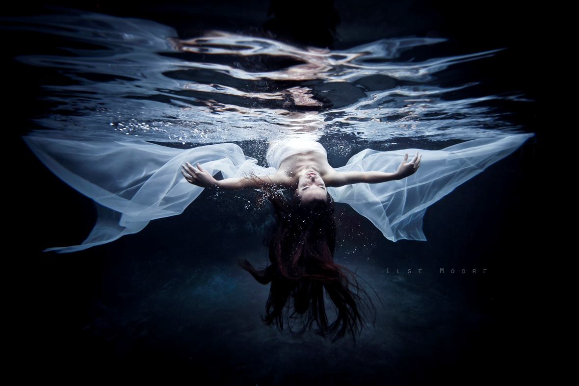"""Figure 1. """"The Immortal"""" by Ilse Moore (n.d.). Reprinted with             permission. A female body lies just beneath the surface of a blackened             water background. Her eyes are shut. Her face is turned up towards the             surface and her arms are outstretched along her side. The woman is wrapped             in a white chiffon scarf which floats around her arms like angel wings."""