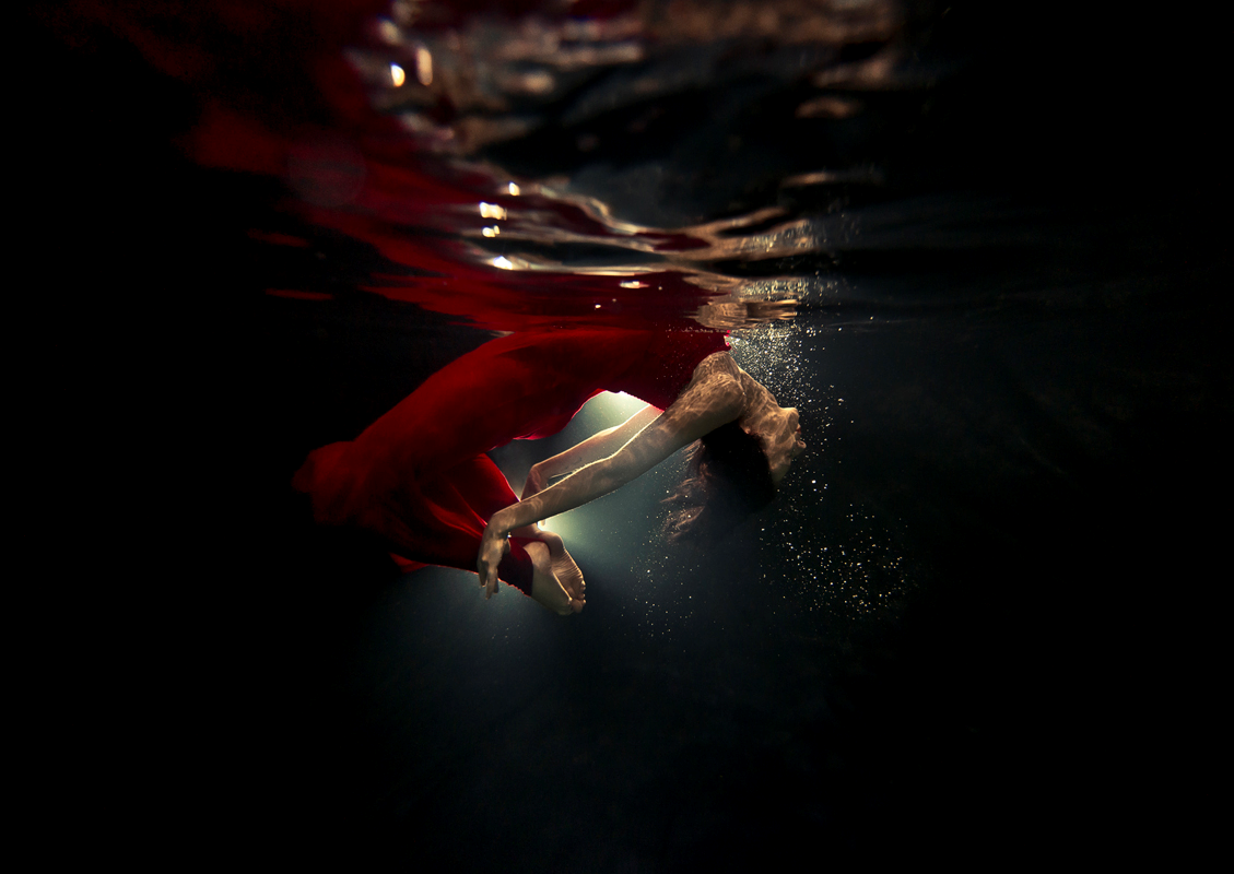 """Figure 2. """"Natalia"""" by Ilse Moore (n.d.). Reprinted with permission.           A woman wearing a strapless crimson gown floats in a sea of blackness.           Hands gripping ankles, her back and neck is arched backward, as her chest           skims the surface."""