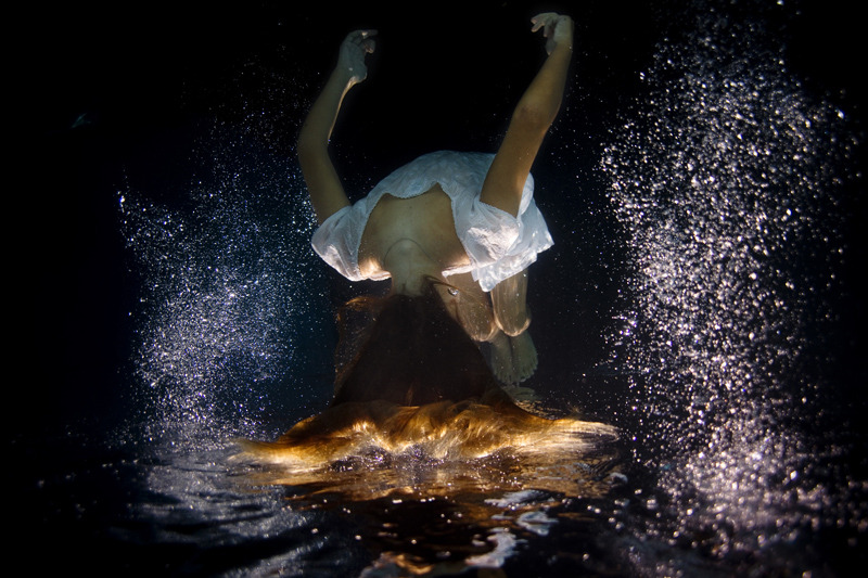 """Figure 3. """"Underwater_dark01"""" by Elena Kalis (n.d.). Reprinted             with permission. A woman wearing a white cotton dress is submerged under             water. Her body is flipped upside down. In contrast to the darkness of             the water, tiny white air bubbles surround the woman's body. Her face cannot             be seen, only the back of her head and long amber hair."""