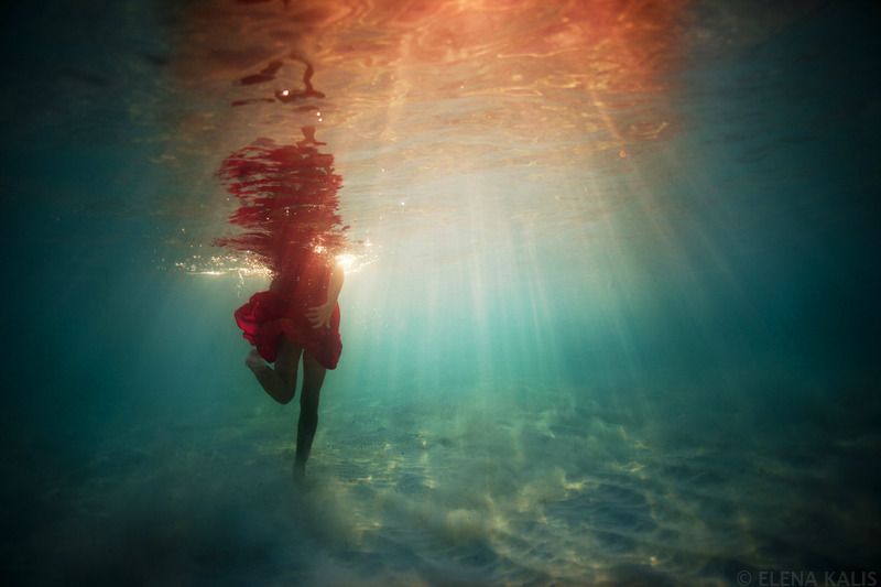 """Figure 7. """"Underwater_elena_kalis55"""" by Elena Kali (n.d.). Reprinted           with permission. A woman is walking along the sandy ocean floor. She is           wearing a short red dress that swirls around her legs. Only the woman's           body can be seen, as her head pokes above the surface. In streaks, light           shines downward through the water's surface in a kaleidoscope of colour."""