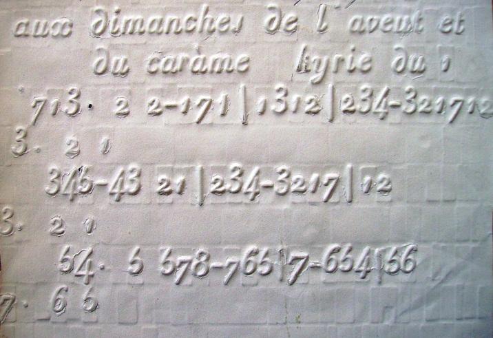 Figure 3. Partition en relief, système Galliod.                Kyrie (début,                               3 premières phrases) de la messe XVII                 Aux Dimanches de l'Avent et du Carême (Paris,                               musée de l'AVH). Sur une feuille blanche le titre «aux dimanches de l'avent                               et du carême, kyrie» est écrit de façon gaufrée en caractères de typographie                               traditionnelle italiques. Il y a une série de chiffres en relief à différentes                               hauteurs sur trois lignes. Des points, des tirets et des barres de mesures                               parsèment ces chiffres.