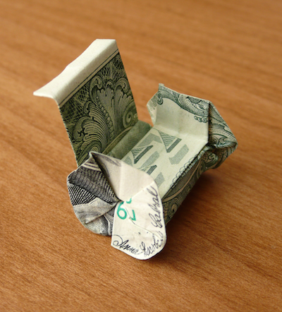 You can click on this image to open the issue. Image depicts a small wheelchair made out of a folded origami dollar bill sitting on a wood table.